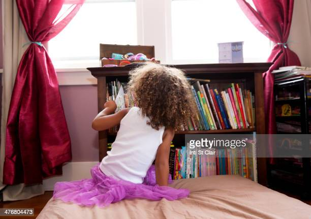 Mixed race girl picking books from shelf