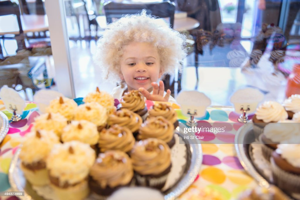 Mixed race girl picking cupcakes in bakery : Stock Photo