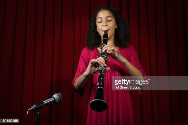 Mixed Race girl playing clarinet on stage