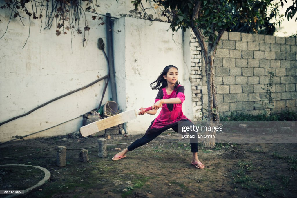 Mixed race girl playing cricket near wall