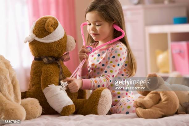 Mixed race girl playing doctor with stuffed animal