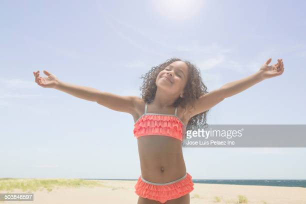 Mixed race girl playing on beach