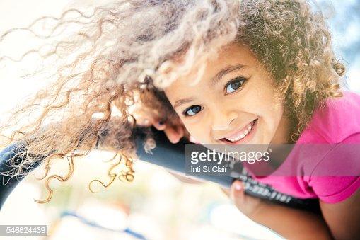 Mixed race girl playing on bicycle rack