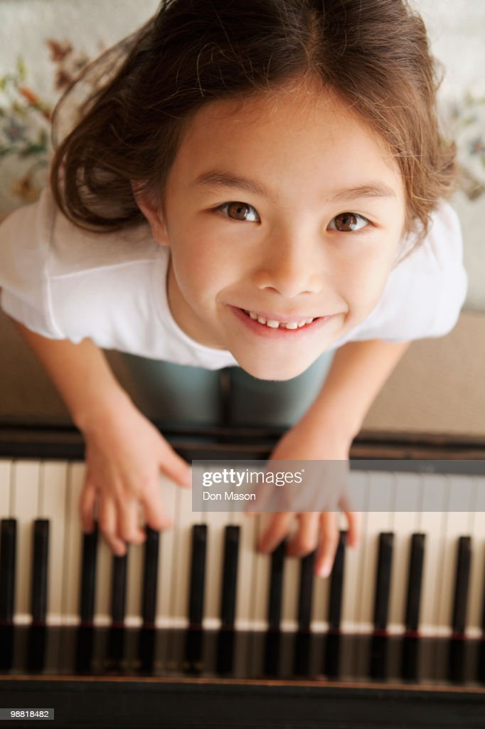 Mixed race girl playing piano : Stock Photo
