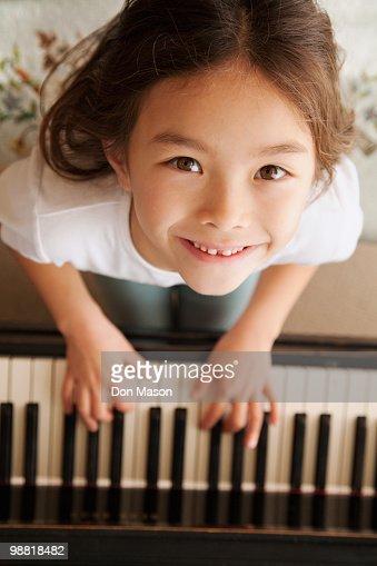 Mixed race girl playing piano : Stock Photo