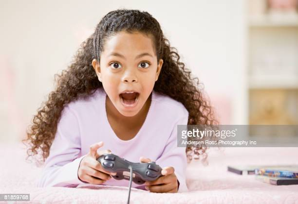 Mixed Race girl playing video game