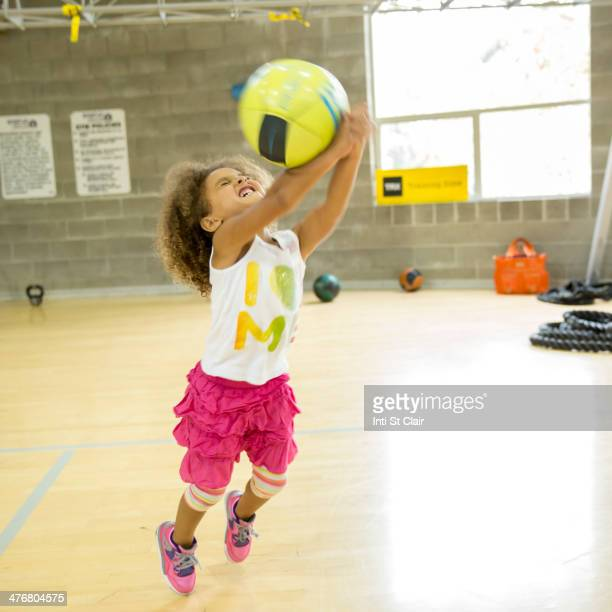 Mixed race girl playing with volleyball on court