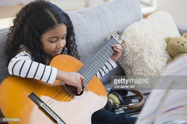 Mixed race girl practicing guitar on sofa