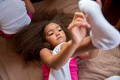 Mixed race girl pulling on sock