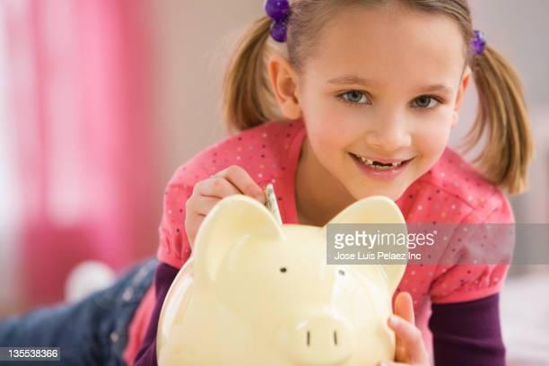 Mixed race girl putting money into piggy bank