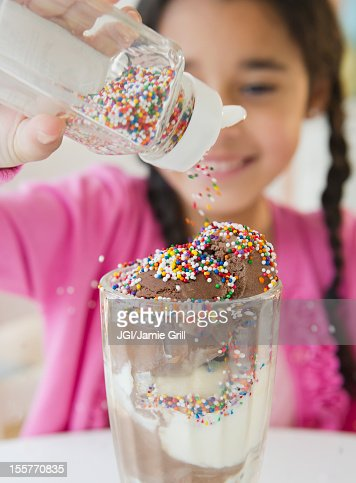 Mixed race girl putting sprinkles on ice cream
