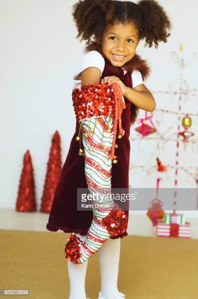 Mixed race girl reaching into Christmas stocking