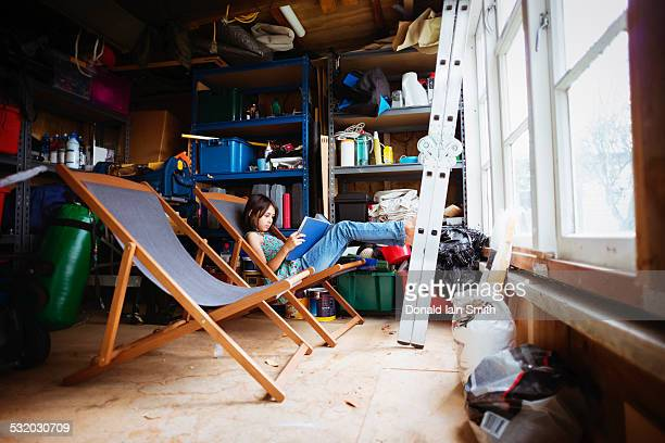 Mixed race girl reading in lawn chair in shed