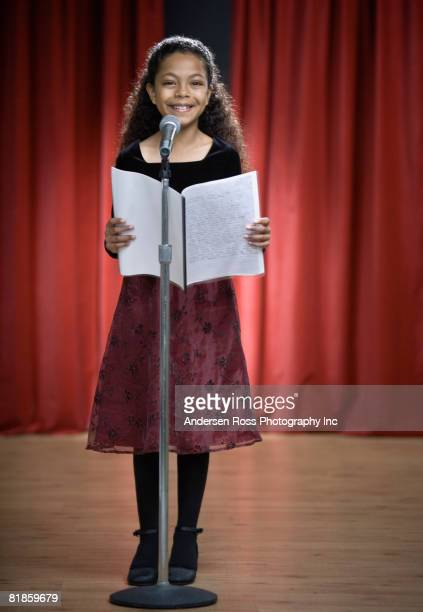 Mixed Race girl reading on stage