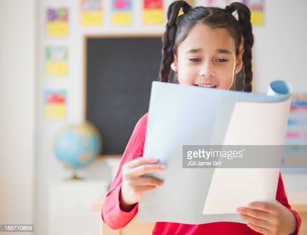 Mixed race girl reading report in school