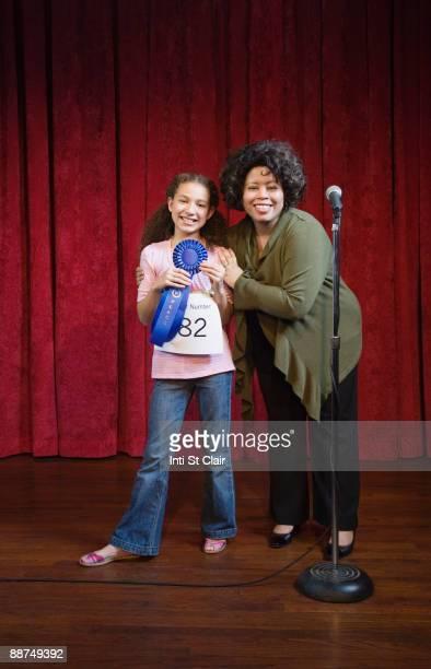Mixed race girl receiving blue ribbon
