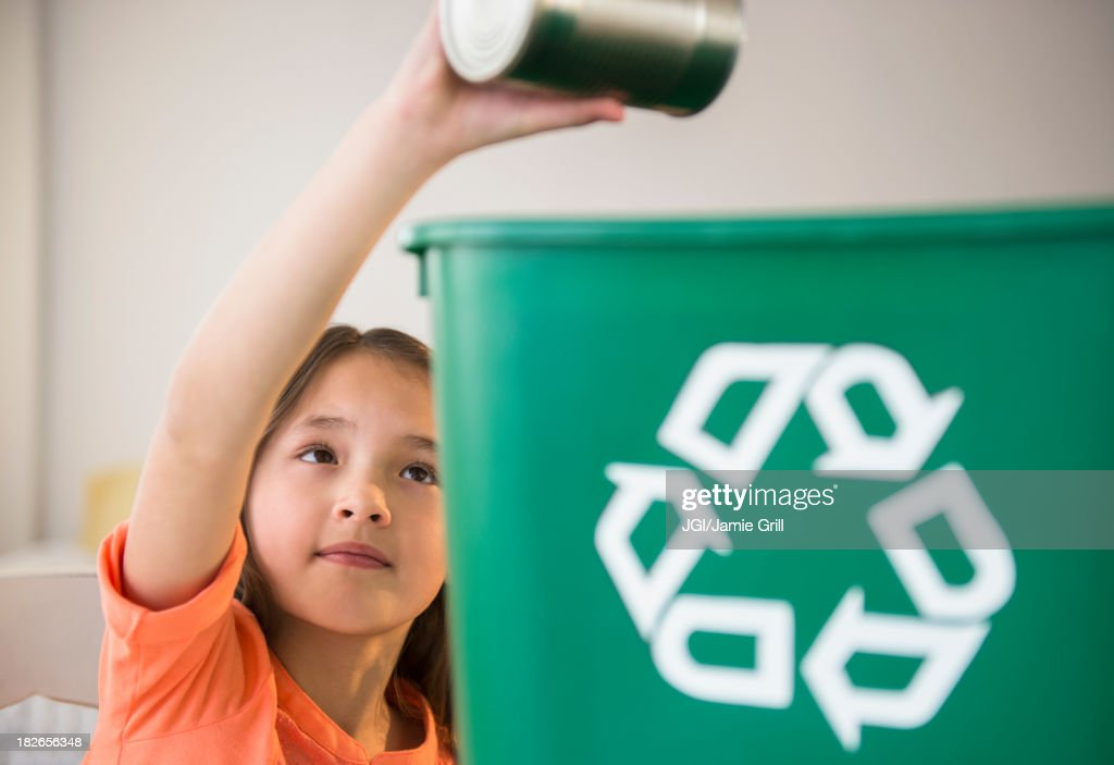 Mixed race girl recycling can