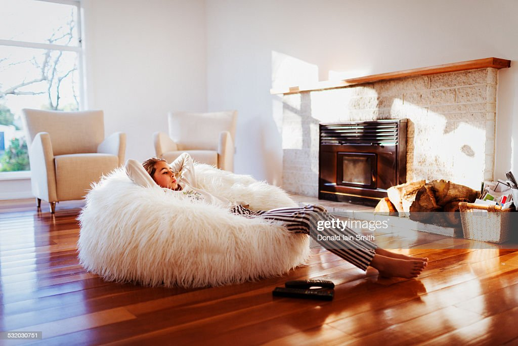 Mixed Race Girl Relaxing In Beanbag Chair In Living Room Stock ...