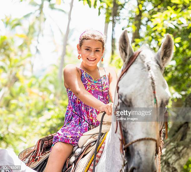Mixed race girl riding horse in jungle