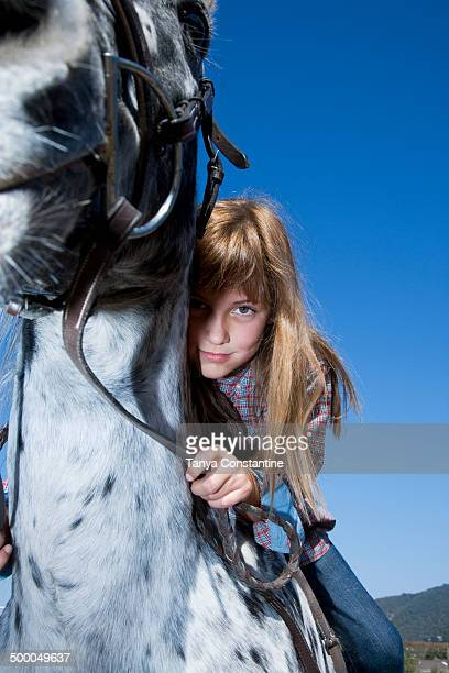 Mixed race girl riding horse on ranch
