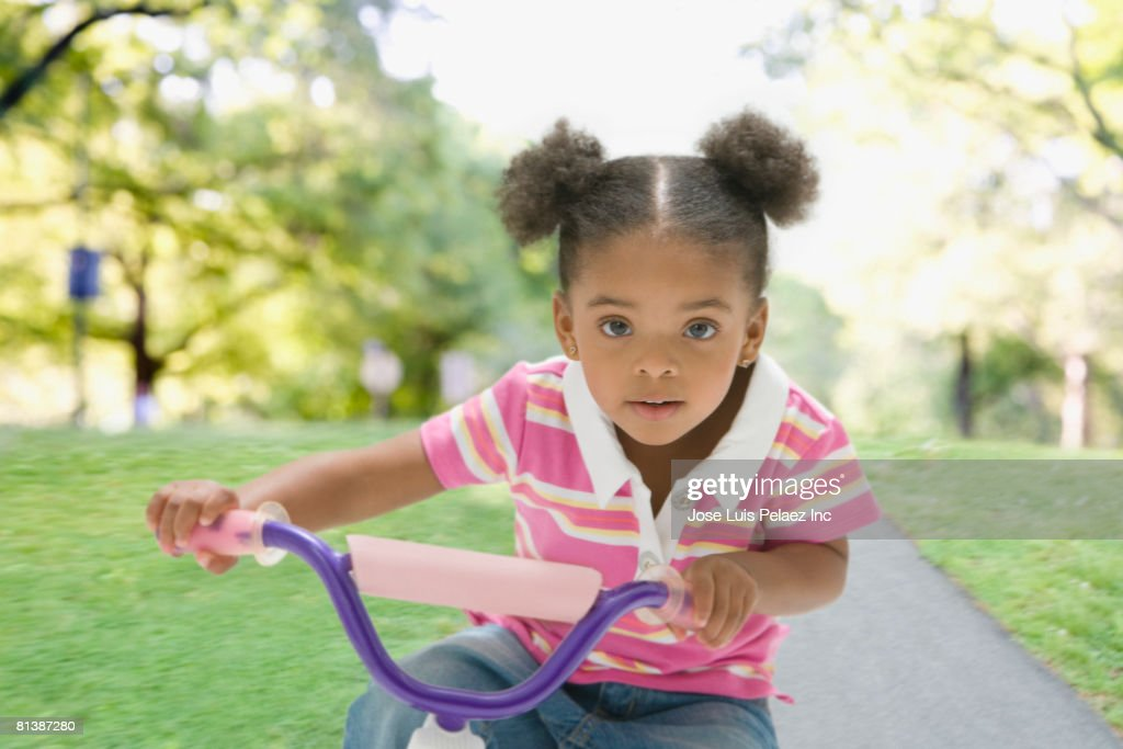 Mixed Race girl riding tricycle : Stock Photo