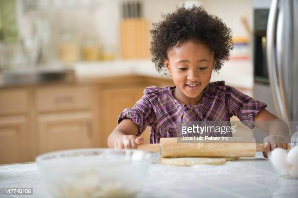 Mixed race girl rolling out dough
