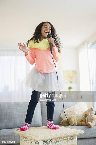 Mixed race girl singing on living room table