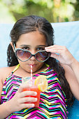 Mixed race girl sipping juice at poolside