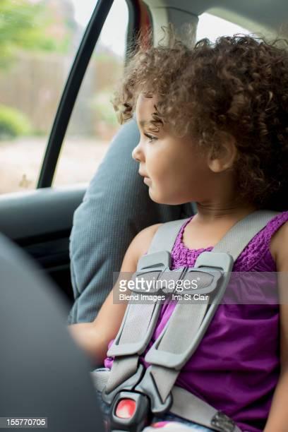 Mixed race girl sitting in car seat