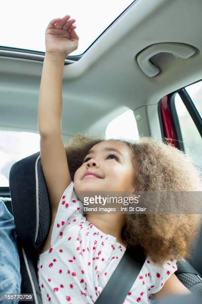 Mixed race girl sitting in car seat with arm out window