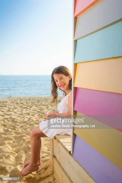 Mixed race girl sitting near colorful beach hut