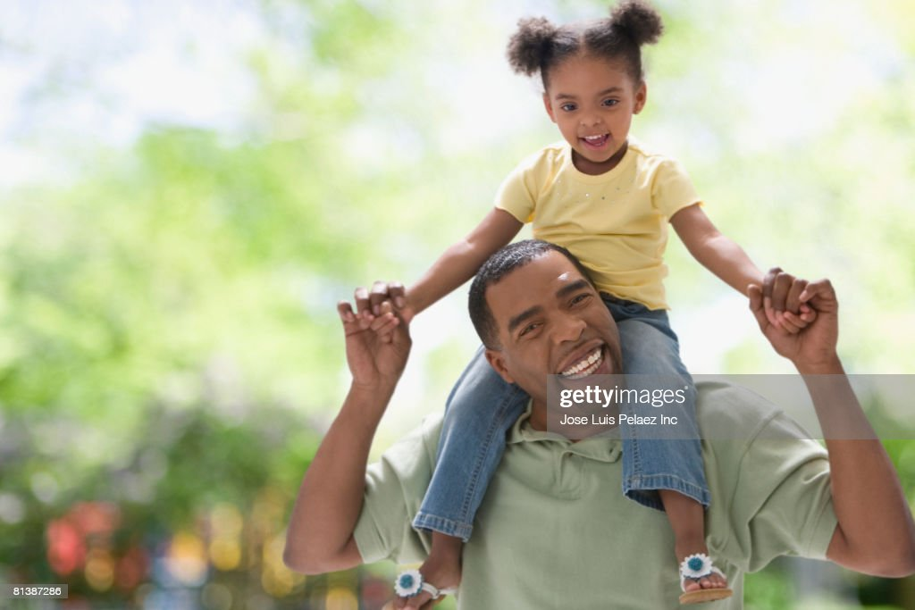 Mixed Race girl sitting on father?s shoulders : Stock Photo