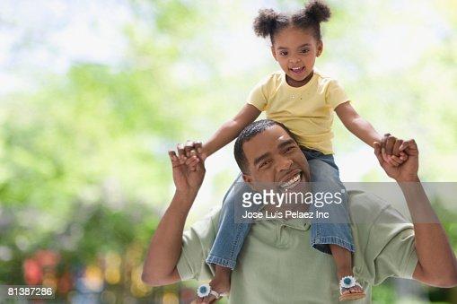 Mixed Race girl sitting on father?s shoulders : Bildbanksbilder