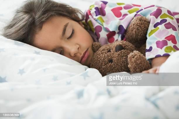 Mixed race girl sleeping in bed with teddy bear