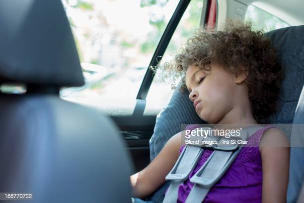 Mixed race girl sleeping in car seat