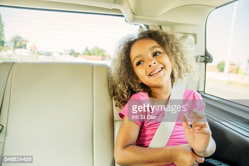 Mixed race girl smiling in back seat of car