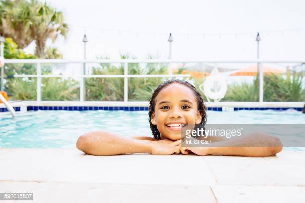 Mixed race girl smiling in swimming pool
