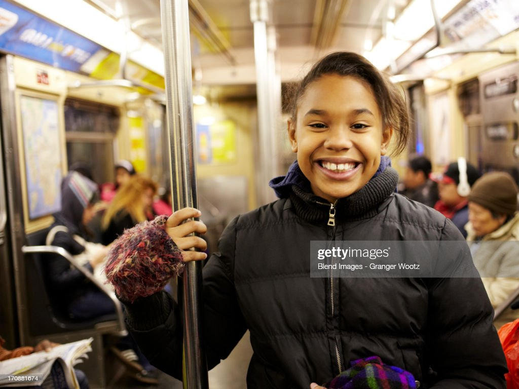 Mixed race girl smiling on subway