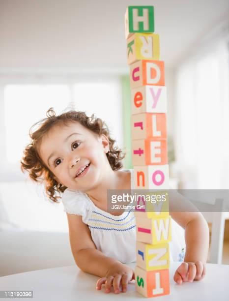 Mixed race girl stacking blocks