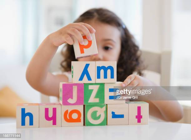 Mixed race girl stacking blocks