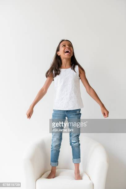 Mixed Race girl standing barefoot on armchair and shouting
