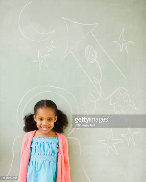 Mixed race girl standing by drawings on blackboard