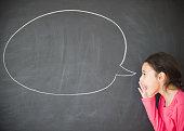 Mixed race girl standing by speech bubble on blackboard