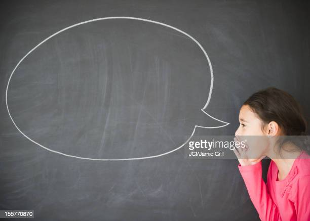 Mixed race girl standing by speech bubble on blackboard