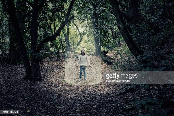 Mixed race girl standing in beam of light in forest