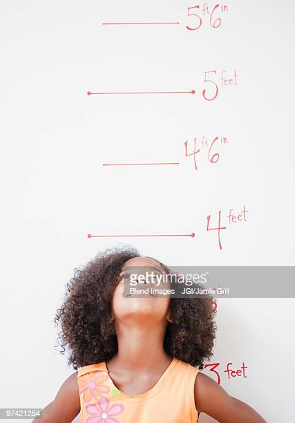 Mixed race girl standing near height chart