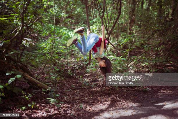Mixed race girl swinging from tree branch on dirt path