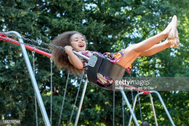 Mixed race girl swinging