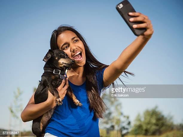 Mixed race girl taking selfie with dog