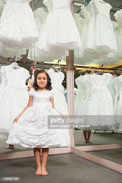 Mixed race girl trying on white dress